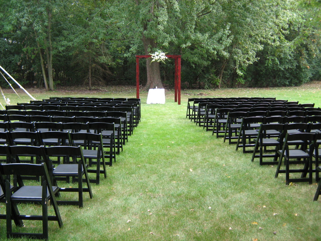 small backyard wedding ideas ceremony with black chairs and simple altar